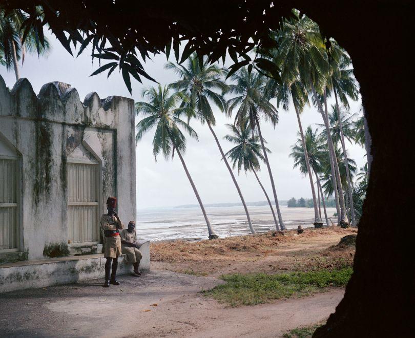 Tanganyika (Tanzania), 1958 – Tanganyika police officer and man next to a wall near the Indian Ocean coastline © 2021 Todd Webb Archive
