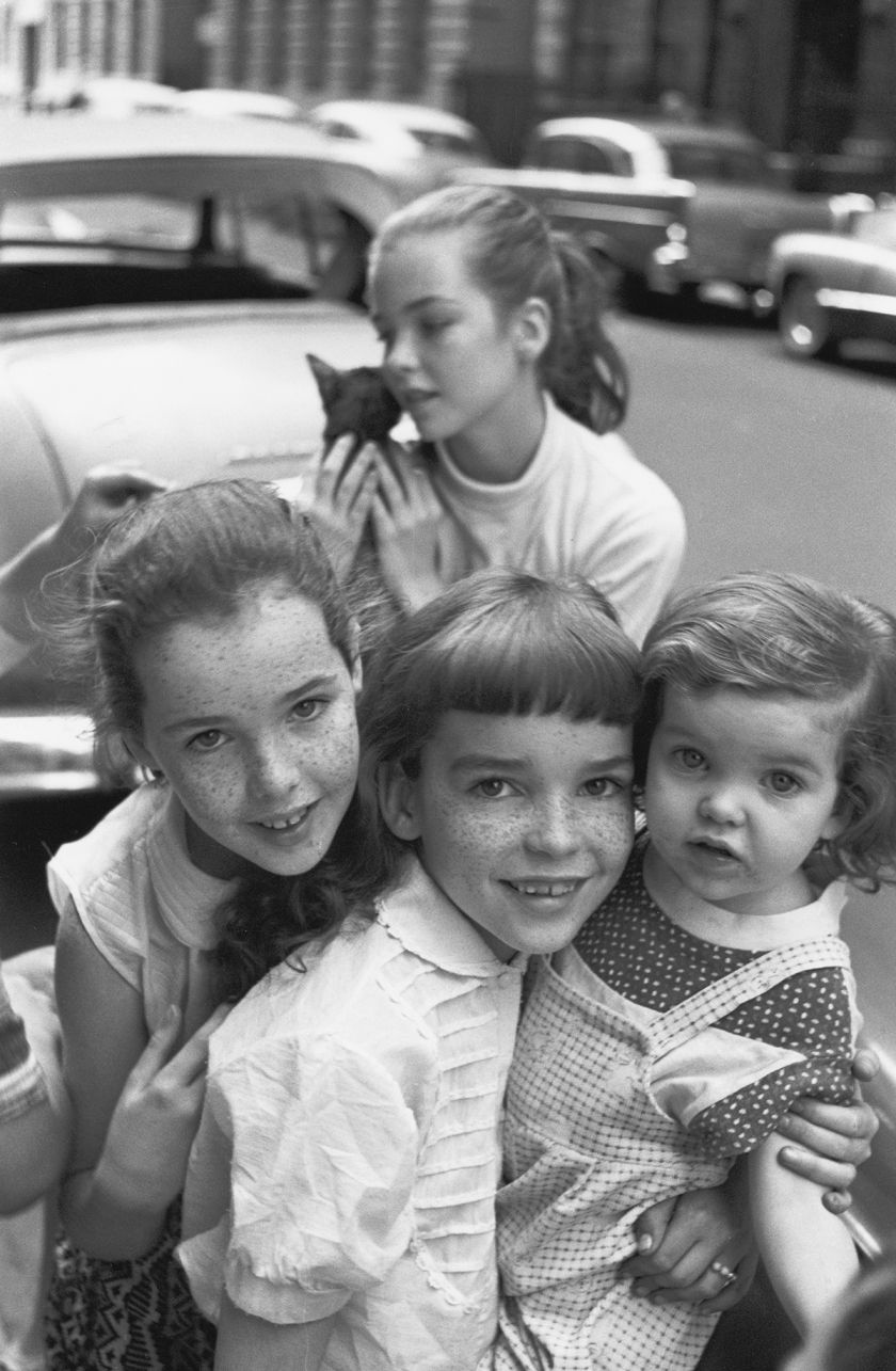 Four related girls, one holding a cat, 1957