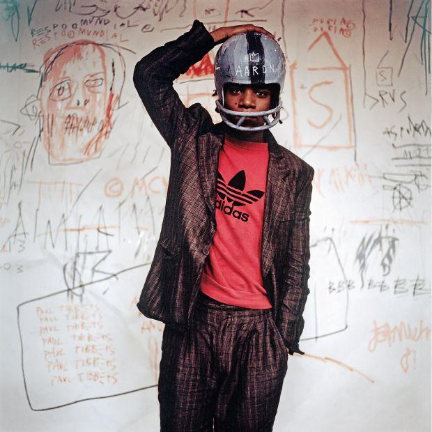 Edo Bertoglio. Jean-Michel Basquiat wearing an American football helmet, 1981 | Photo: © Edo Bertoglio, courtesy of Maripol. Artwork: © The Estate of Jean-Michel Basquiat. Licensed by Artestar, New York