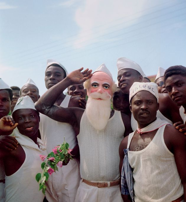 "Togoland (Togo), 1958 – Group of men with white hats, one with the slogan ""Ablode"" (freedom), and another with a Santa Claus mask on election day, April 27 © 2021 Todd Webb Archive"