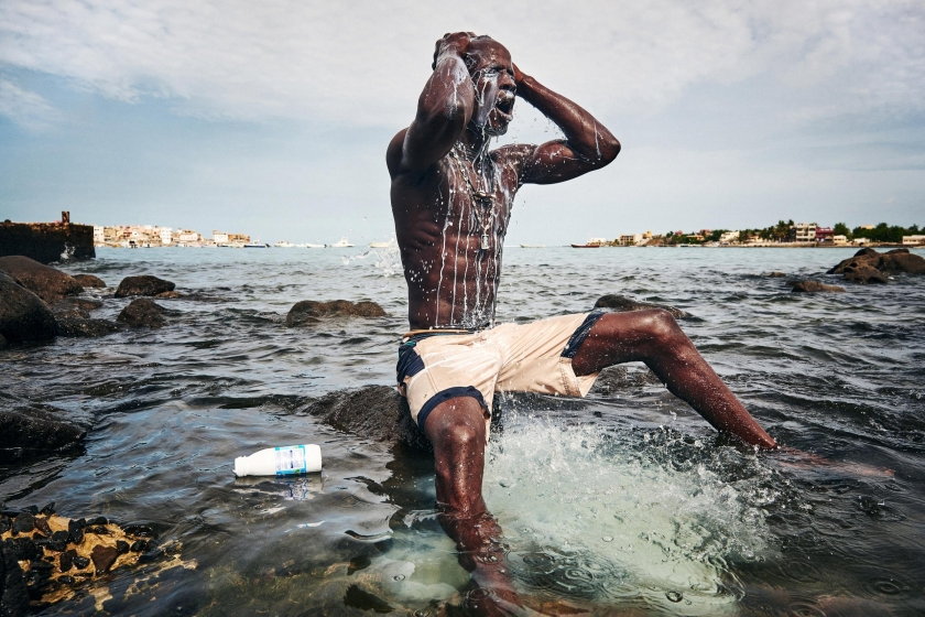 Sports, second prize stories: Kherou, a young wrestling champion, performs a ritual in the water of the sea while pouring milk over his body in order to obtain the reinforcement of a ghost who lives in the stones at the shore. Christian Bobst.