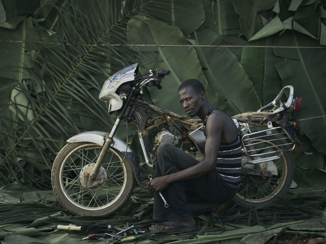 Kempah Ginnah, 42, youth leader and mechanic with his own motorbike, in the village of Tombohuaun. Because he has a bike, he is asked to give people lifts to the health centre. Kailahun District, Sierra Leone, May 2017. WaterAid/ Joey Lawrence