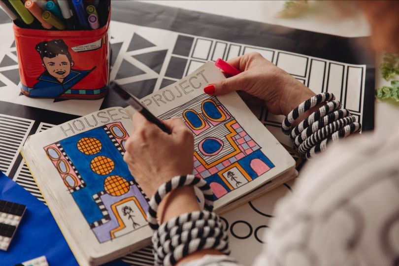 Shot of Camille Walala drawing in her sketchbook at her studio, working on the newly launched installation for LEGO DOTS. Photo credit Dunja Opalko.
