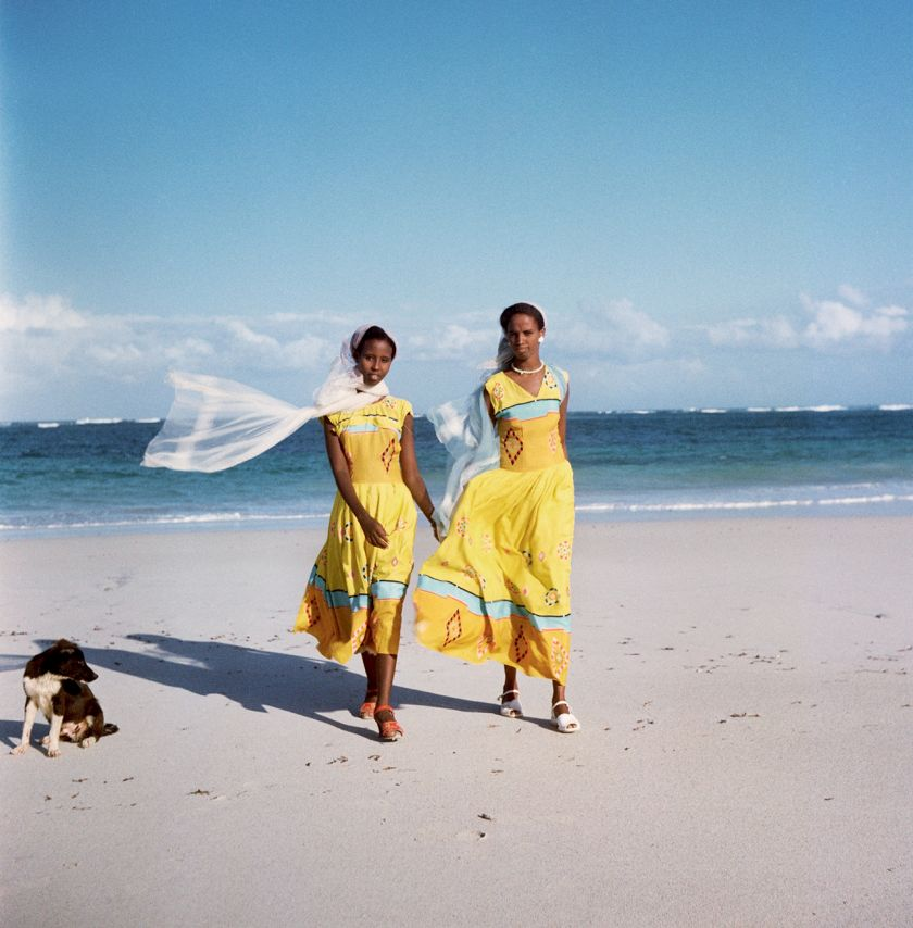 Trust Territory of Somaliland (Somalia), 1958 – Two women walking on the beach, with a dog to their right © 2021 Todd Webb Archive