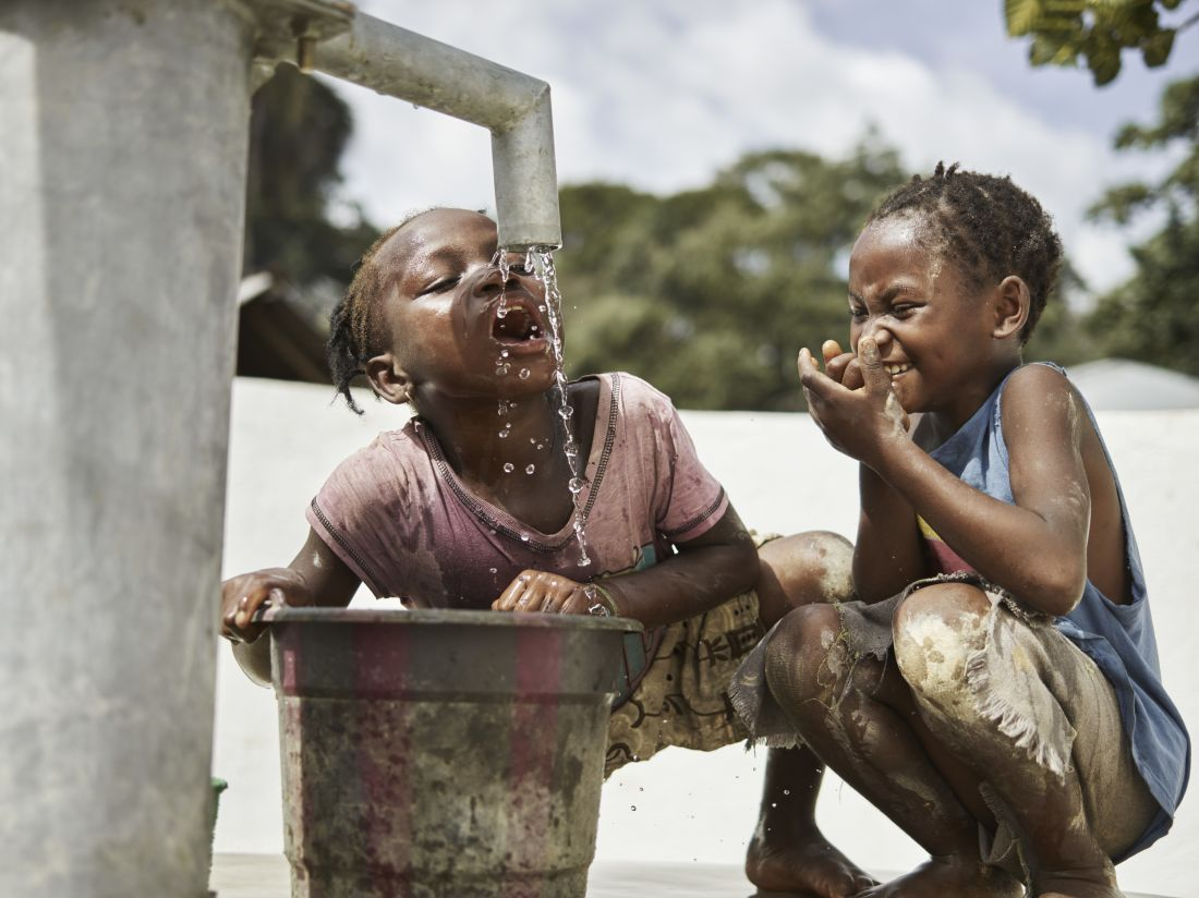 Batu, 10, left, and Madie, 8, play in clean water at the pump in Tombohun, Sierra Leone, May 2017. WaterAid/ Joey Lawrence