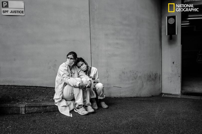Taking a brief break during ceaseless frontline work treating patients with the coronavirus, nurses Caroline Quinet (at left) and Yasmina Cheroual rest outside CHU Ambroise Paré hospital. The pair, who had known each other for only a few months, pulled long shifts in the intensive care unit. Like many medical facilities around the world, Belgian hospitals initially were overwhelmed by a rush of patients with the virulent, ever changing new disease. These nurses, pulled from their standard duties, were thrown into full-time COVID-19 work—reinforcement troops for a long, exhausting battle. (Cédric Gerbehaye/National Geographic)