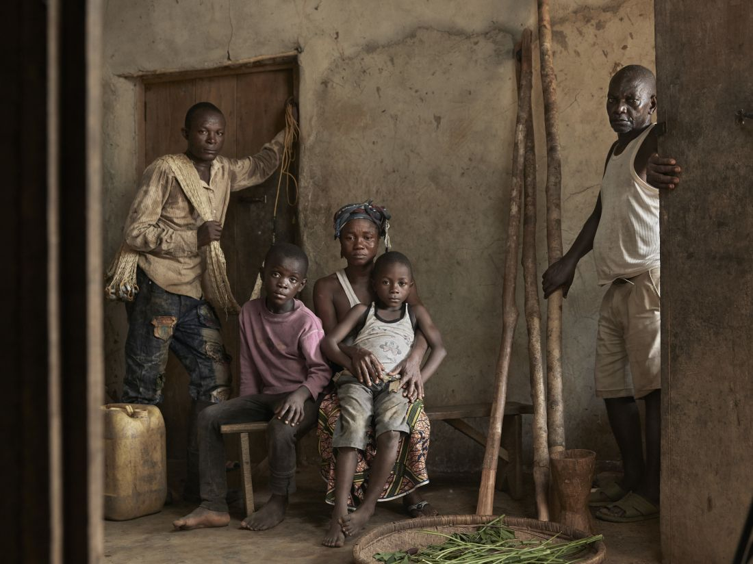 Joe, 6, sitting on the lap of Mariatu, his mother, with the rest of the family posing for a group portrait, at their home in the village of Tombohuaun, Kailahun District, Sierra Leone, May 2017. WaterAid/ Joey Lawrence