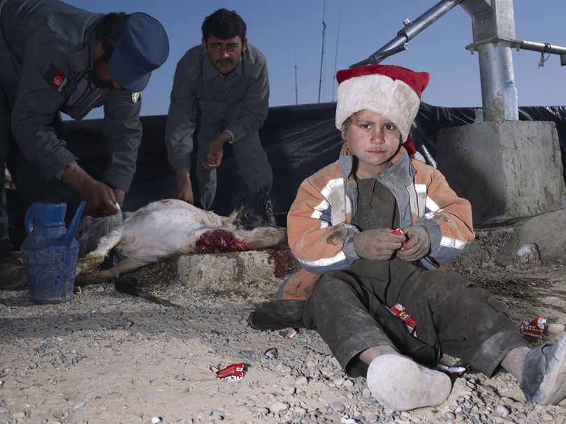 Mark Neville, 'Child, Jacket, Slaughtered Goat, Sweets, Painted Nails, Xmas Day, Helmand', 2010, courtesy Mark Neville