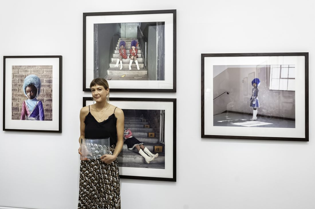 First prize winner, Alice Mann, with her portraits. Photograph by Jorge Herrera.