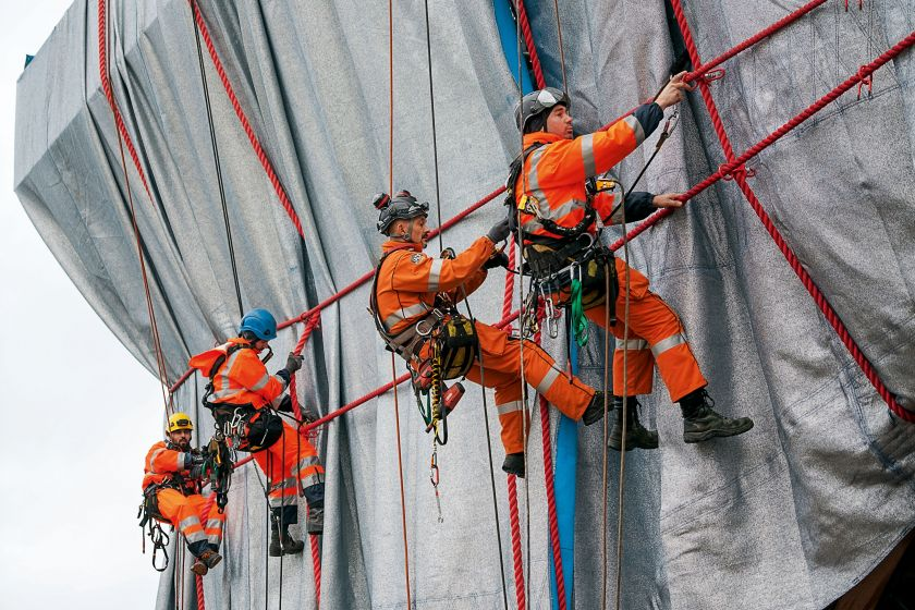 """Professional climbers from Compagnie des Guides de Chamonix link the ropes to steel rope connectors, which are attached through """"button holes"""" in the fabric to the steel structure."""