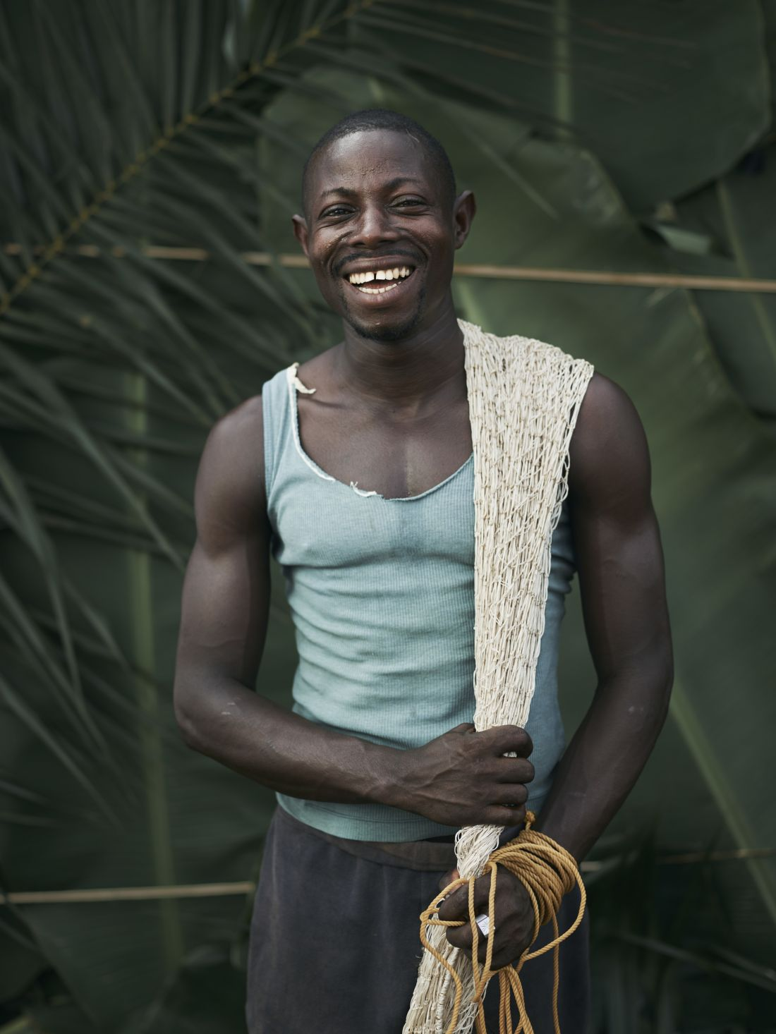Sellu Smart, holding home-made fishing nets, made from leaves, in the village of Tombohuaun. Sellu spends at least half of his wages on healthcare for his family. If he didn't have to he would develop his farm by increasing the yield, and do more business such as buying palm oil or selling clothes. Kailahun District, Sierra Leone, May 2017. WaterAid/ Joey Lawrence