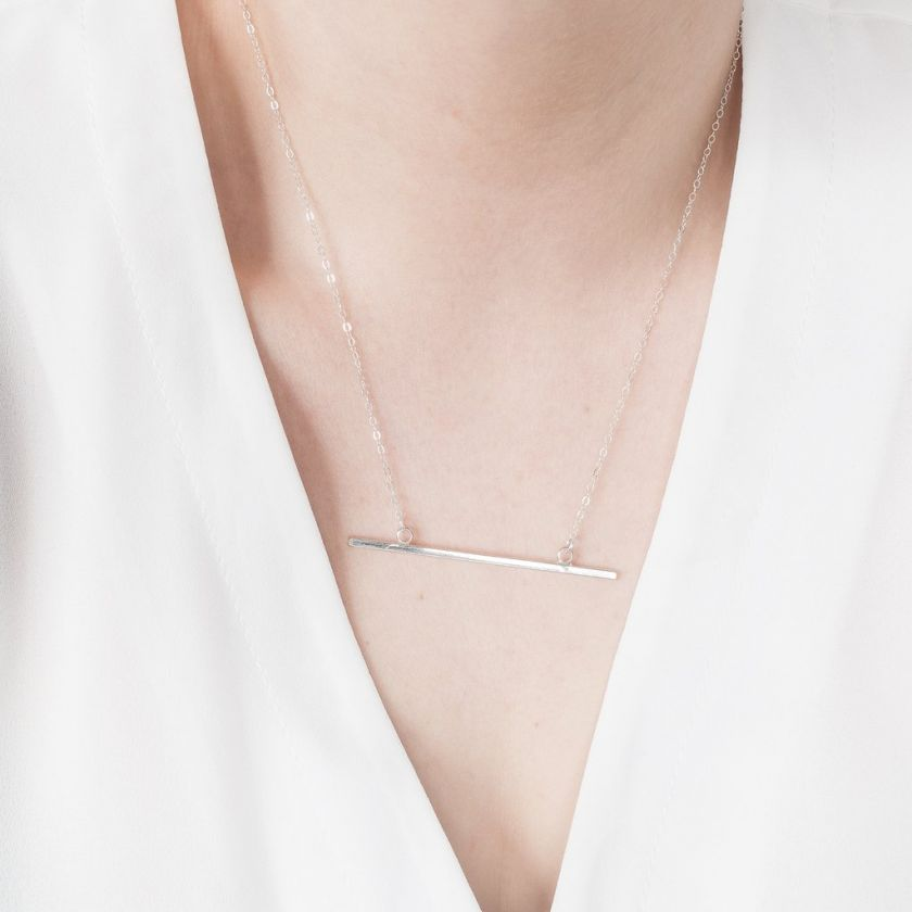 Minimal Bar necklace by [OMCH](https://www.ohmyclumsyheart.com/collections/necklaces/products/sterling-silver-horizontal-bar-necklace). Priced at £27