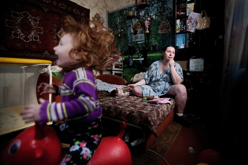 Local Family - Anton Unitsyn: Oksana and her two kids. Over 50% of their small salary is spent for utilities. They own this little room in the old house. Girl with ginger hair - Sothia, was born with heart disease. (Professional Daily Life)