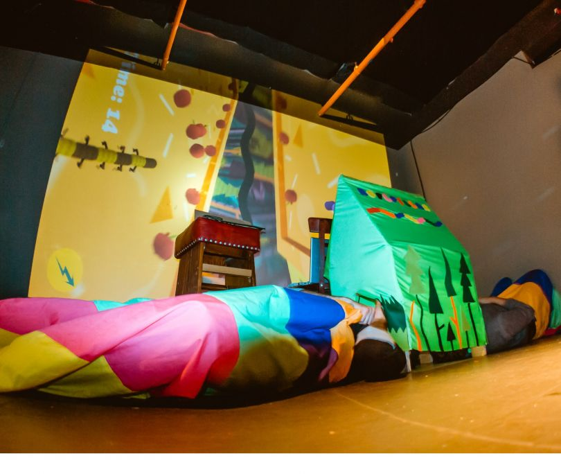 Roflpillar: Two players dress as rainbow-coloured caterpillars and wriggle around on the floor, competing to collect the most apples. The game's screen is fixed to the roof inside the fabric playhouse where players stick their heads. Image: Lucky Frame