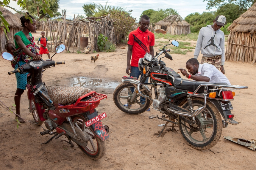 """Some guys repairing their motorbikes in front of their """"Kimbo"""" where they live, south Angola"""