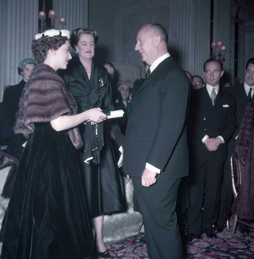 Princess Margaret (left), with the Duchess of Marlborough behind, presents Christian Dior with a scroll entitling him to Honorary Life Membership of the British Red Cross after the presentation of his Winter Collection at Blenheim Palace on 3rd November 1954. © Popperfoto / Getty Images