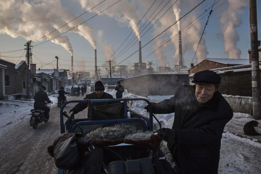 Daily Life, first prize singles: Chinese men pull a tricycle in a neighborhood next to a coal-fired power plant in Shanxi, China. Kevin Frayer.