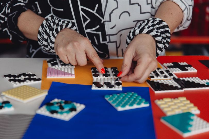 Behind the scenes shot of Camille Walala playing with the new LEGO DOTS range in her studio. Photo credit Dunja Opalko.