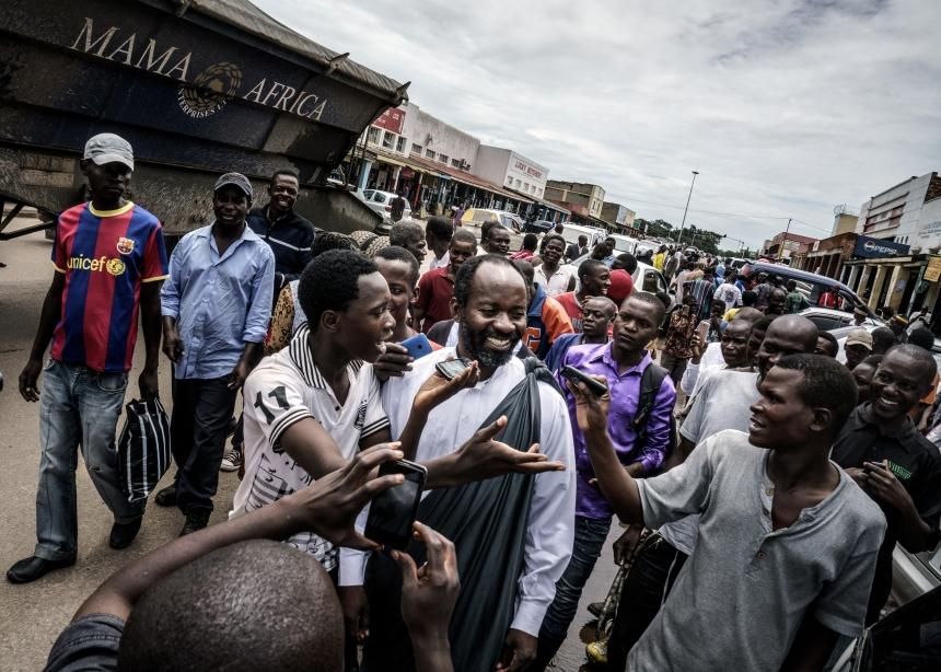 Jesus of Kitwe (born Mupeta Chishimba) proselytizing in a market place. Big crowds gather, recording his every word on their mobile phones. Zambia, 2015   © Jonas Bendiksen/ Magnum Photos