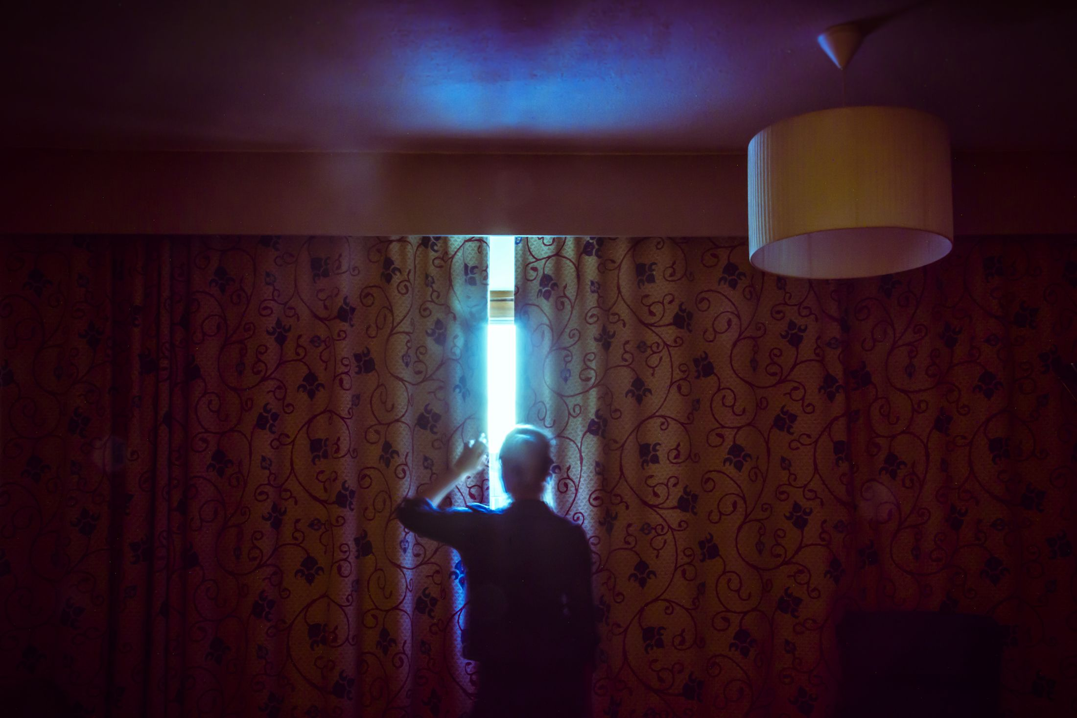 A photo of a person peaking through the curtains in their living room. The room is fairly dark - you can barely make out a vine pattern on the curtains, and it is bright outside, so the brightness is almost blinding.