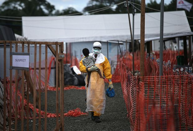 Copyright: John Moore / Getty Images. An MSF health worker in protective clothing carries a sick girl at an Ebola treatment centre.