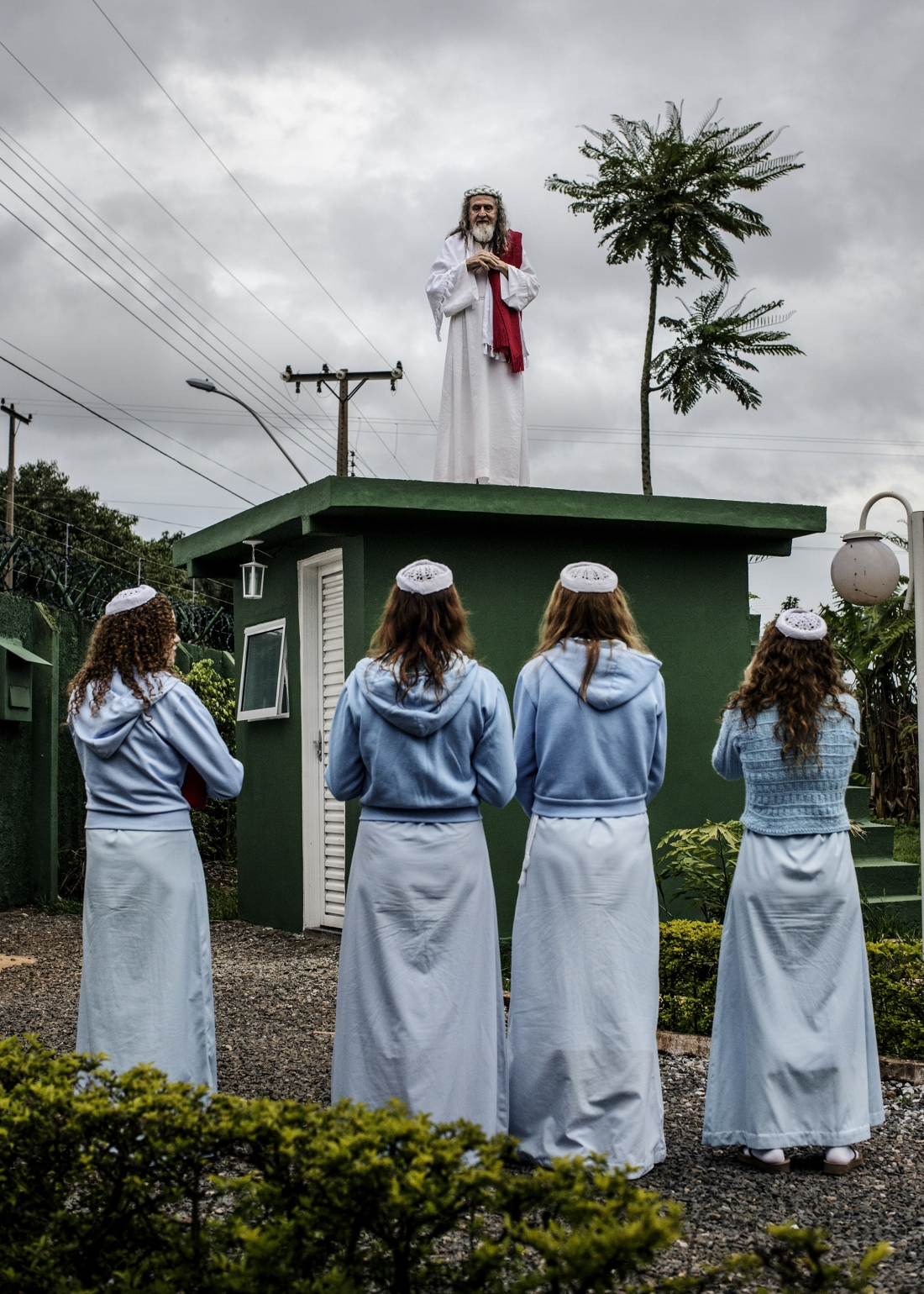 INRI Cristo preaches to his followers from the top of the compound guardhouse. The disciples live a quiet and secluded life inside the compound, growing most of their own food and focussing on INRI's mission. Brazil, 2014 | © Jonas Bendiksen/ Magnum Photos
