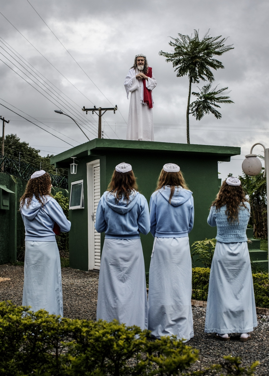 INRI Cristo preaches to his followers from the top of the compound guardhouse. The disciples live a quiet and secluded life inside the compound, growing most of their own food and focussing on INRI's mission. Brazil, 2014   © Jonas Bendiksen/ Magnum Photos