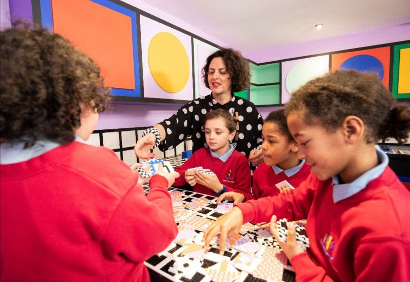 Workshop with kids at Camille Walala's new installation for LEGO, celebrating the launch of DOTS. Photo credit Getty Images.