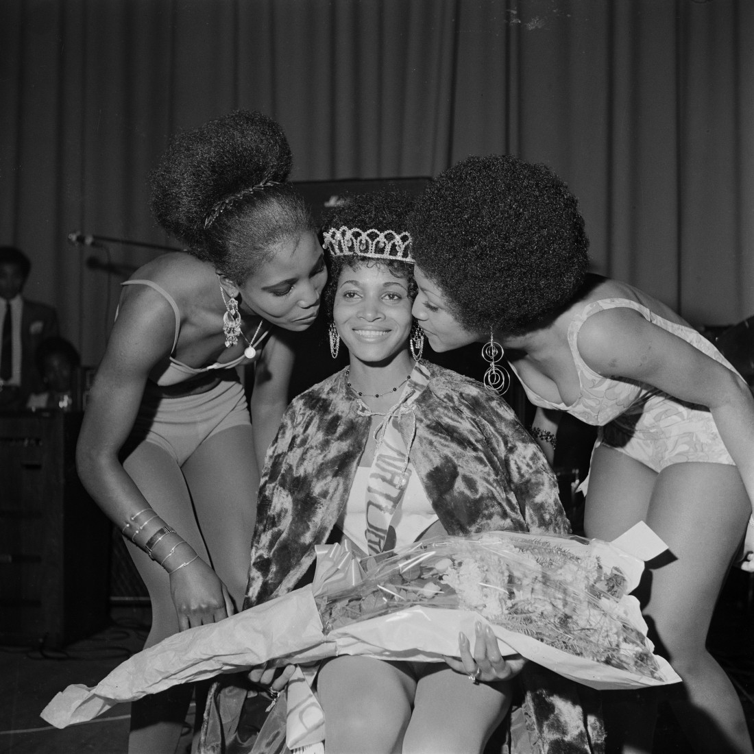 'Miss Black & Beautiful Rhona Williams with fellow contestants, Hammersmith Palais, London, 1970s.                                                                    From the portfolio 'Black Beauty Pageants'.                                          Courtesy of © Raphael Albert/Autograph ABP