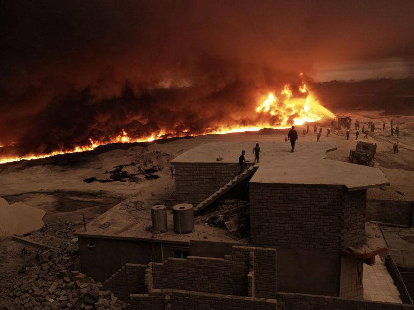 A family watches from their rooftop as firefighters struggle to extinguish a wall of flames creeping closer to their home. Qayyarah, Nineveh Governorate, Iraq, October 26, 2016. From [We Came From Fire](https://amzn.to/2L9l8Vm) by Joey L. – published by powerHouse Books