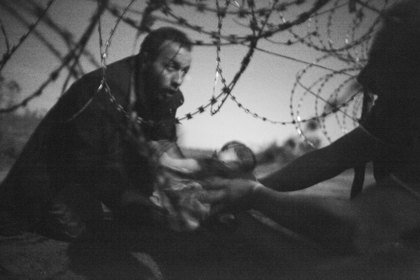 World Press Photo of the Year: A man passes a baby through the fence at the Hungarian-Serbian border in Röszke, Hungary, 28 August 2015. Warren Richardson.