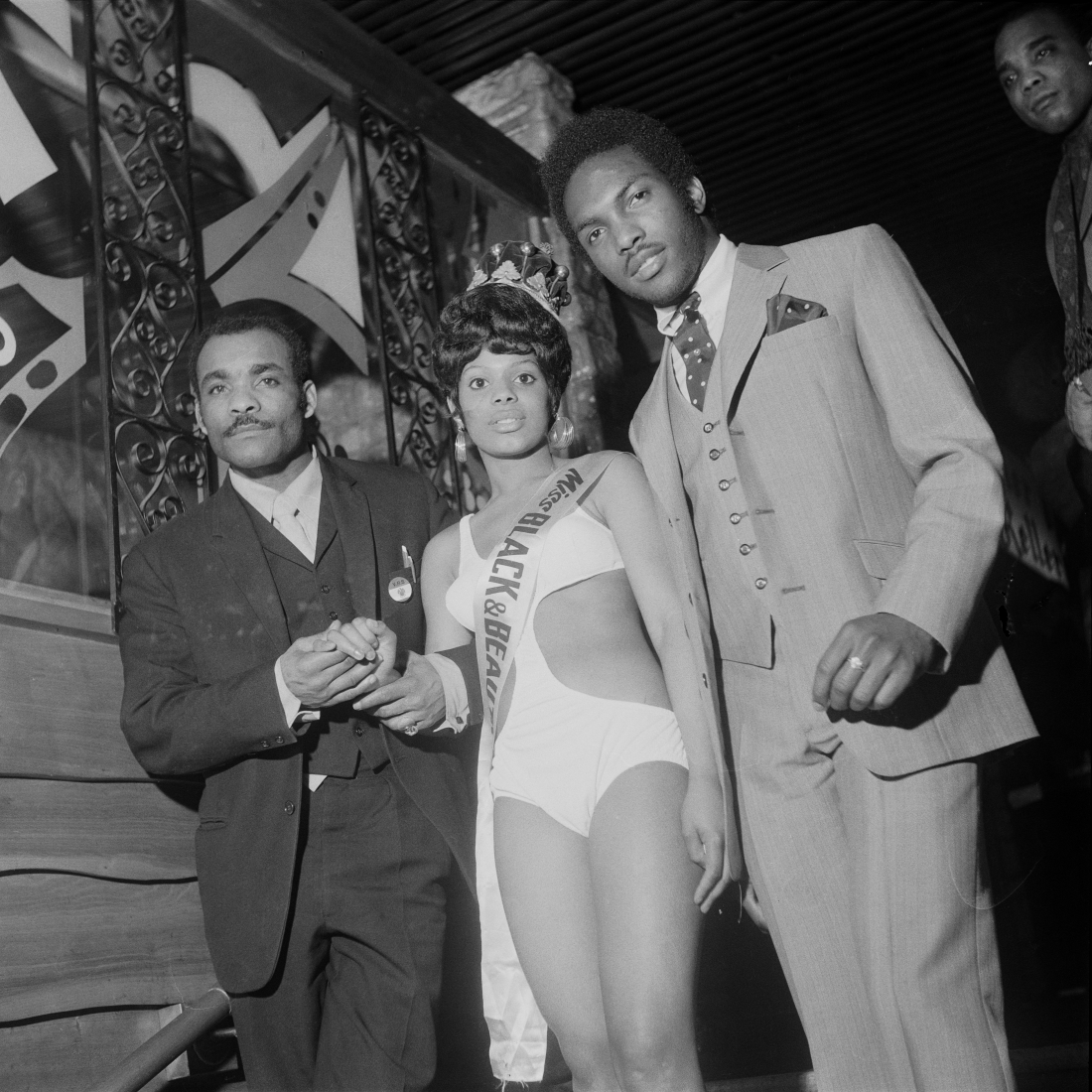 (unidentifed) Miss Black & Beautiful escorted by two men, Hammersmith Palais, London, 1970s. From the portfolio 'Black Beauty Pageants'. © Raphael Albert, courtesy Autograph ABP
