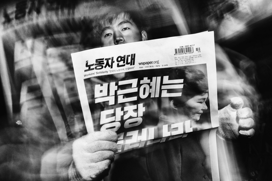 "Read All About It. During a cold winter evening, a man sells Workers' Solidarity newspapers to protesters marching towards the presidential Blue House. The headline reads: ""Park Geun-hye Resign Now."" © Argus Paul Estabrook. Street Series Winner, Magnum and LensCulture Photography Awards 2017"