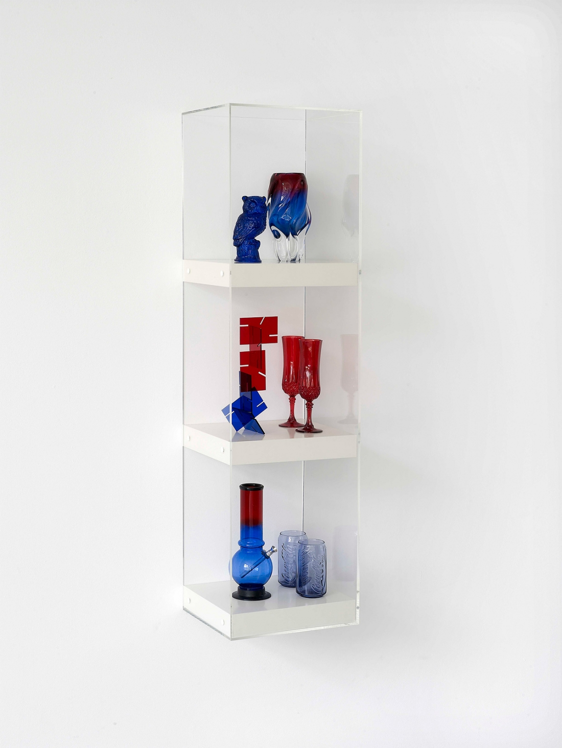 Matthew Darbyshire Untitled: Shelves No. 7 (Series 2) 2010 Resin cast owl figurine, Murano vase, acrylic desk sculpture, crystal d'arque champagne flutes, acrylic bong, McDonald's Coca Cola glasses, shelves, Perspex case 120 × 30 × 30 cm Courtesy of the artist and Herald St, London