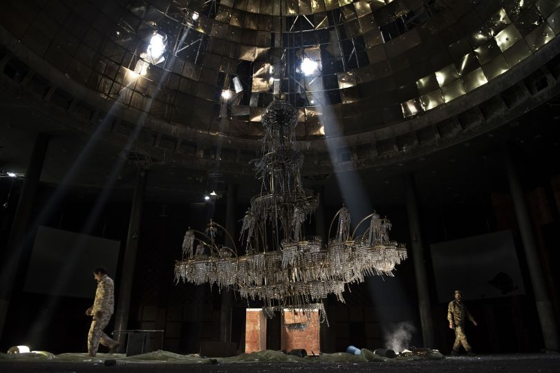Libya, July 14, 2016: Fighters of the Libyan forces affiliated with the Tripoli government walk around the gigantic chandelier of the conference room in the Ouagadougou conference centre | © Alessio Romenzi, Italy, Shortlist, Professional, Current Affairs & News, 2017 Sony World Photography Awards