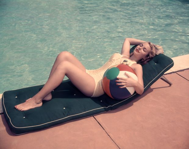 UNITED STATES - Circa 1950s: Woman Sun Bathing On Green Mat By Edge Side Of Pool Water Recline Holding Beach Ball By Her Side Relax. © H. Armstrong Roberts / Getty Images