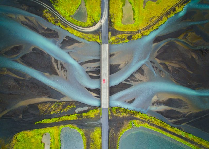 Aerial view of Glacial river in Iceland. While crossing the bridge, I noticed some pattern in the water and wondered how it would look from the sky. I stopped the car at a turnout after crossing the bridge and flew my drone to capture this image. I included the bridge and the car to give an idea of the scale. This river flows to the ocean and becomes part of the sea.  Copyright: © Manish Mamtani, India, Shortlist, Open, Travel (Open competition), 2018 Sony World Photography Awards