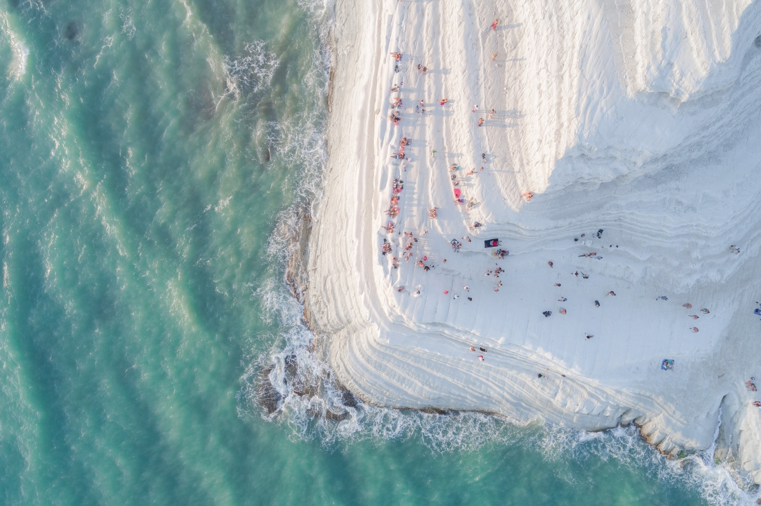 """""""Scala dei Turchi"""" (The Turkish Steps) is a white cliff in Realmonte (Sicily) made of a soft limestone and a blinding white marl. Natural erosion has created steps on the cliff face, making it look soft and sinuous, like a Big Meringue covered with sprinkles (the people sitting and walking on it). Only after shooting this image, while watching it on a bigger screen, I noticed a newlywed couple in the frame kissing for their wedding photoshoot. Exactly at the edge of the cliff. Copyright: © Placido Faranda, Italy, Shortlist, Open, Landscape & Nature (2018 Open competition), 2018 Sony World Photography Awards"""