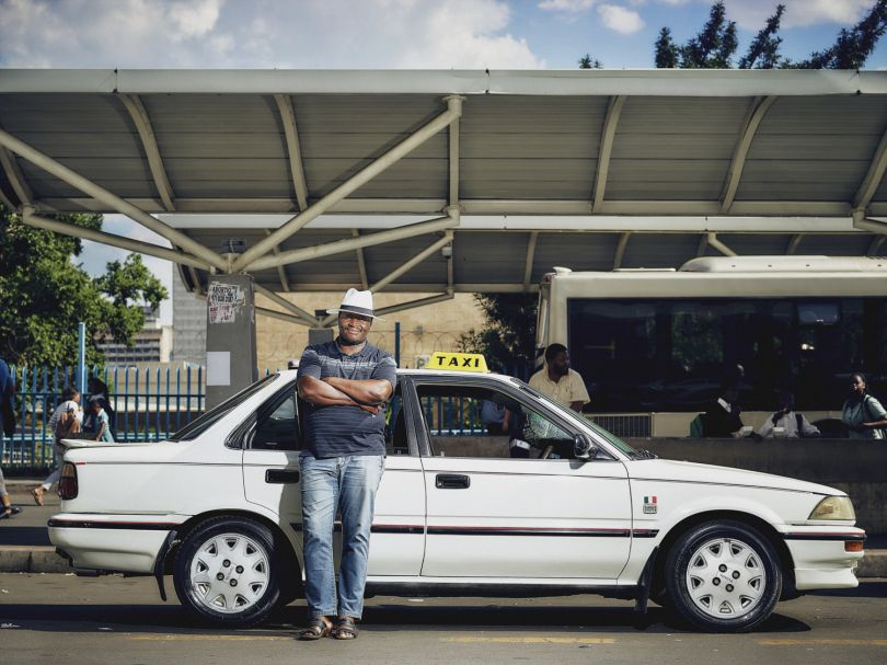 """""""People like the cheaper transport and Uber is cheap - cheap like buying bread! I used to have 11-12 trips a day, now, since Uber, it's more like 6-7. But Uber drivers are brothers of Africa - I can't do anything to them, the problem is the owner of Uber. The government of South Africa are very, very dumb - it is they who have caused the problem - Zuma is like Mugabe!   I would like to say this to the head of Uber: 'Uber must go back to San Fransisco. They are not welcome - they are bulldozing our business and they are like an octopus that wraps their arms around you.' People are saying 'we would rather die' … what's the point!"""" - Michael, Johannesburg. The Uber Impact © Matthew Joseph"""