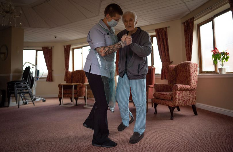 Jack Dodsley, 70, dances with a carer in PPE © Tom Maddick / SWNS
