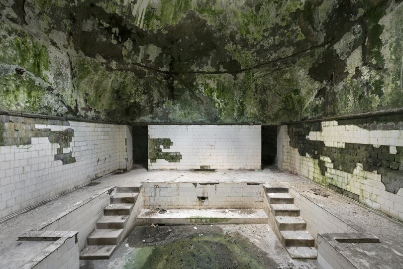 A derelict bathhouse is seen inside the thermal spa town of Tskaltubo. The water still flows through and underneath these baths, causing the buildings to deteriorate even faster. Tskaltubo, Georgia. © Reginald Van de Velde