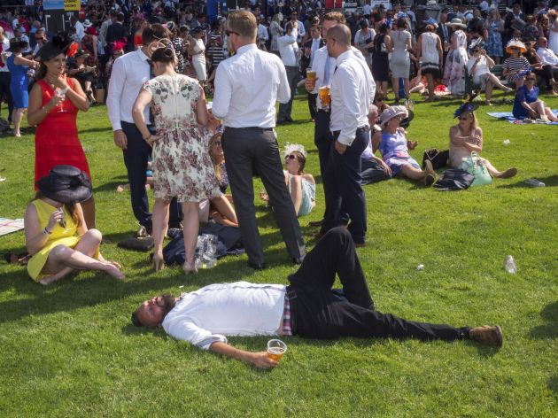 A man with his pint rests on the grass at Royal Ascot. June 2017. All photography courtesy of Peter Dench. © Peter Dench