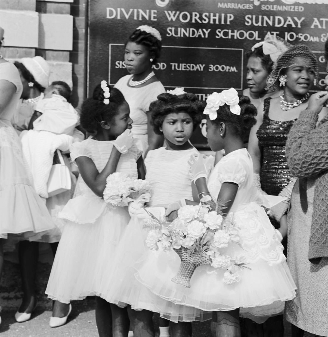 Three young black girls chatting outside a Methodist chapel, 1950-59, © Historic England Archive
