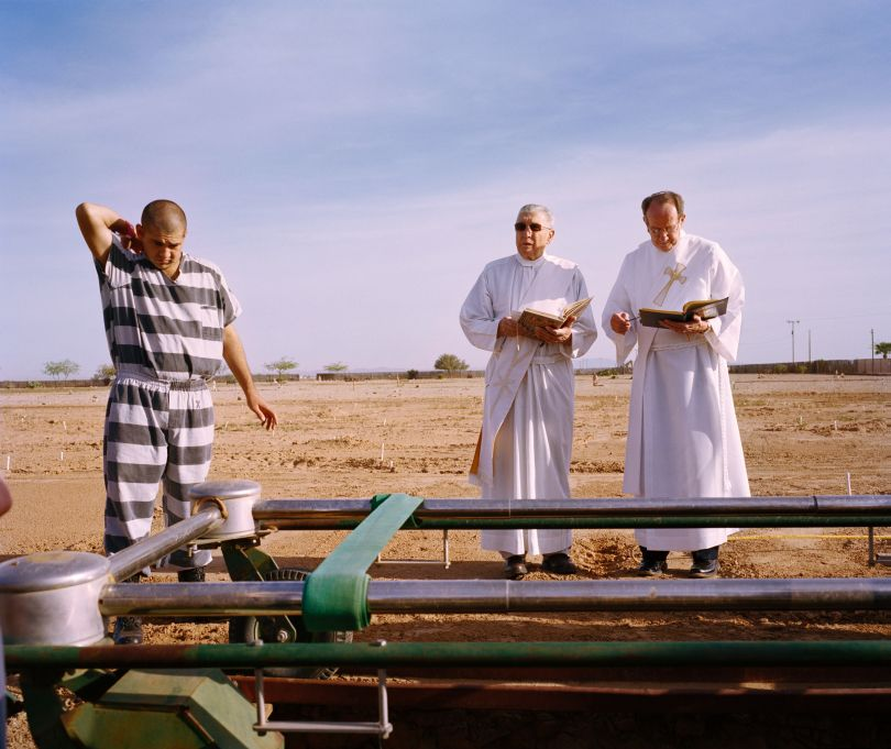 An inmate and two priests during burial duty
