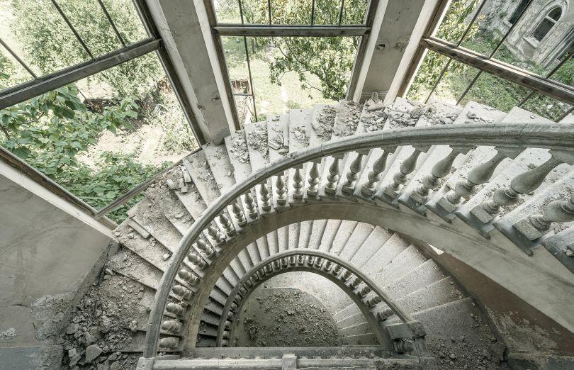 A crumbling spiraling staircase is seen inside this former Soviet sanatorium. Tskaltubo, Georgia. © Reginald Van de Velde