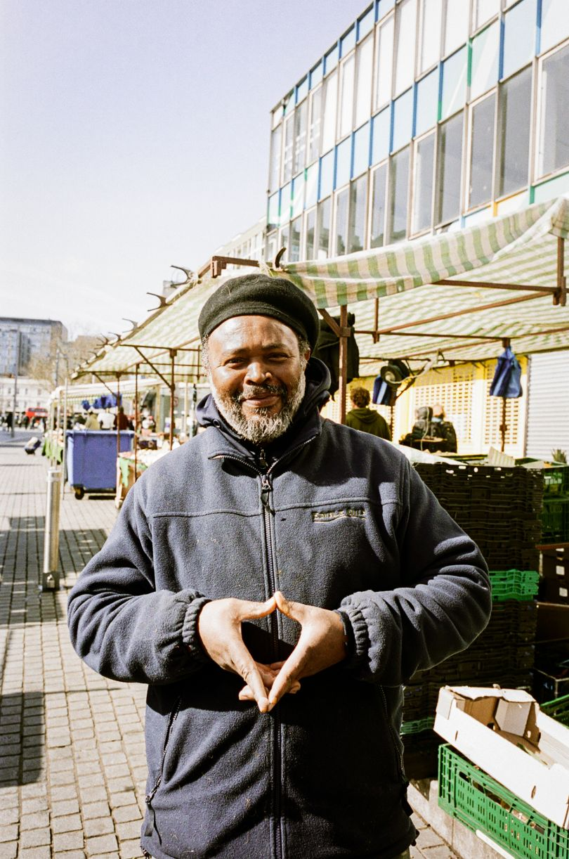Junior in front of Junior's Caribbean stall in Woolwich © Jonas Martinez / Museum of London