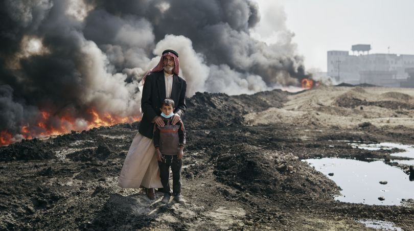 Kharim and his guardian, Nadak, beside a burning oil field. Qayyarah, Nineveh Governorate, Iraq, October 25, 2016. From [We Came From Fire](https://amzn.to/2L9l8Vm) by Joey L. – published by powerHouse Books