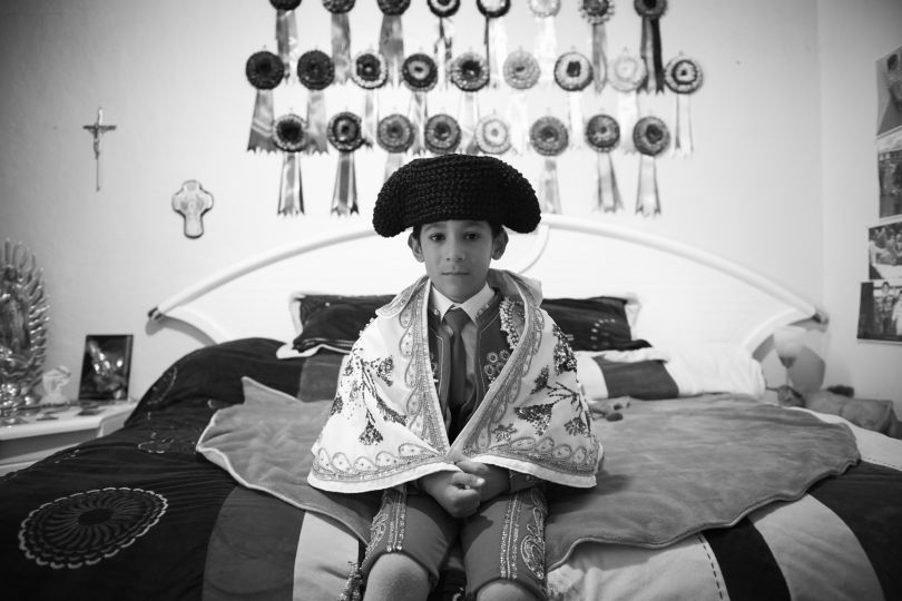 Salvador, aged 6, sits on his bed in anticipation of witnessing the afternoon bullfight at Plaza de Toros Mexico. Behind him are several ribbons, each symbolize a bull dedicated to him by his matador heroes. Salvador's family is wealthy and staunch Catholics. They believe God will protect him from any harm | © Christina Simons, Iceland, Shortlist, Professional, Daily Life, 2017 Sony World Photography Awards