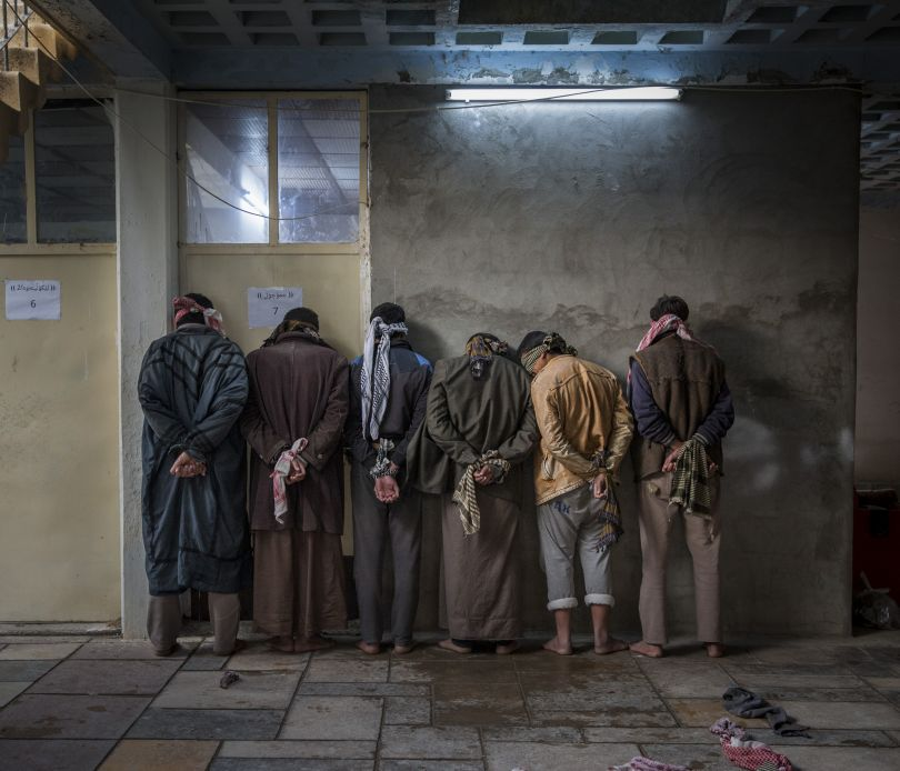 Iraqi men from the Hawija region of Iraq wait to be questioned by Kurdish security personnel at a base near Kirkuk. Having fled areas still under the control of ISIS militants, men and boys of fighting age are vetted for any links to the group before being allowed to join their families in camps for displaced people in the Kurdish controlled region of the country | © Ivor Prickett, Ireland, Shortlist, Professional, Current Affairs & News, 2017 Sony World Photography Awards