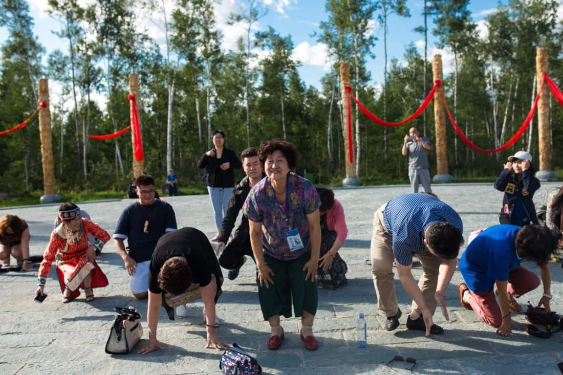 Lower Kingan Mountain Range, Heilongjiang Province, July 2017 Community leader Guan Jinfang leads visiting government representatives in a ritual praying for fortune from a newly constructed monument to shamanism.